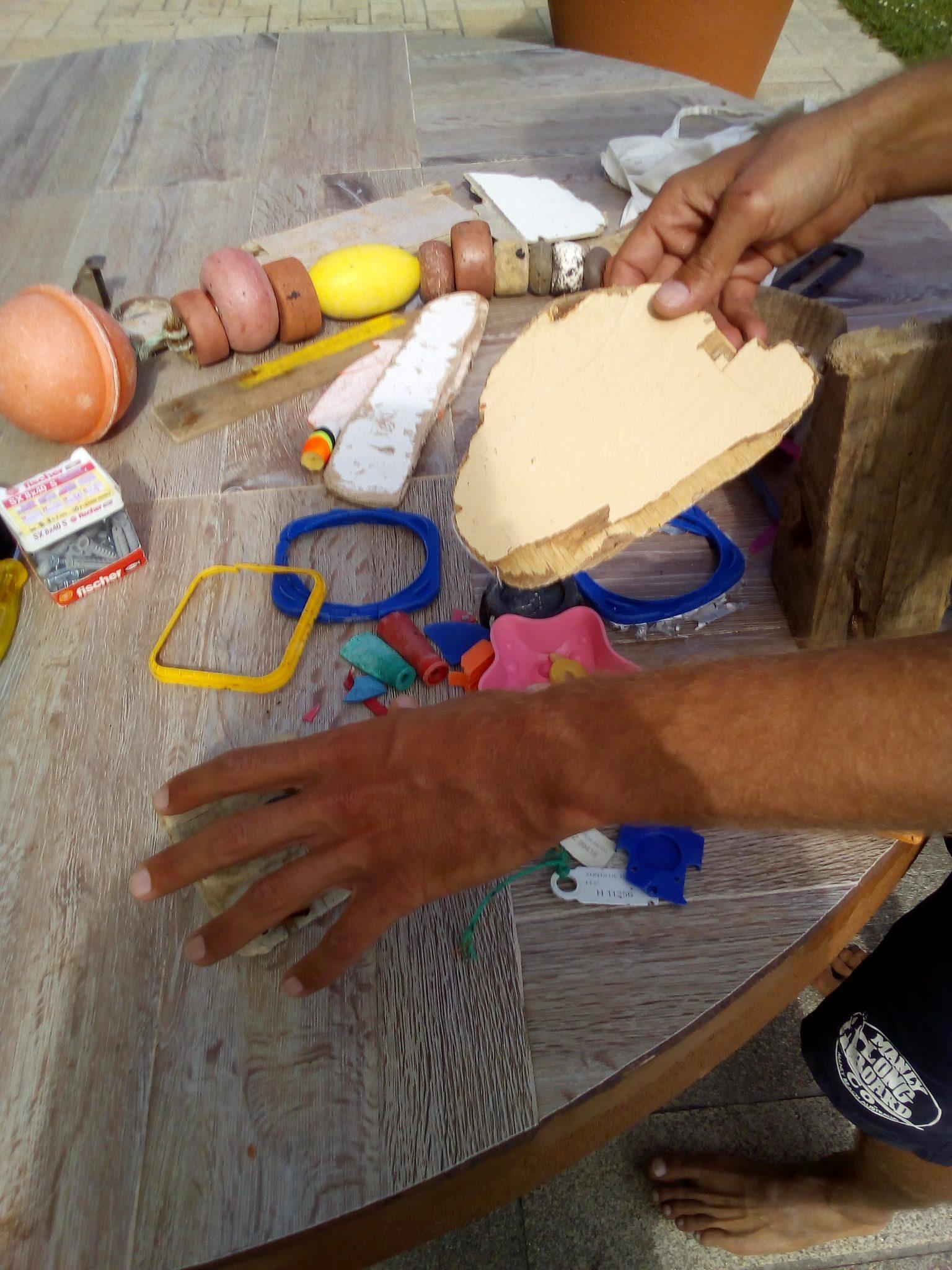 Dann sortiert er Holzplanken und Plastikteile.